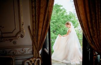 Erstaunliche Braut in einem Hochzeitskleid wirft auf dem Balkon in einem Luxushotelzimmer auf