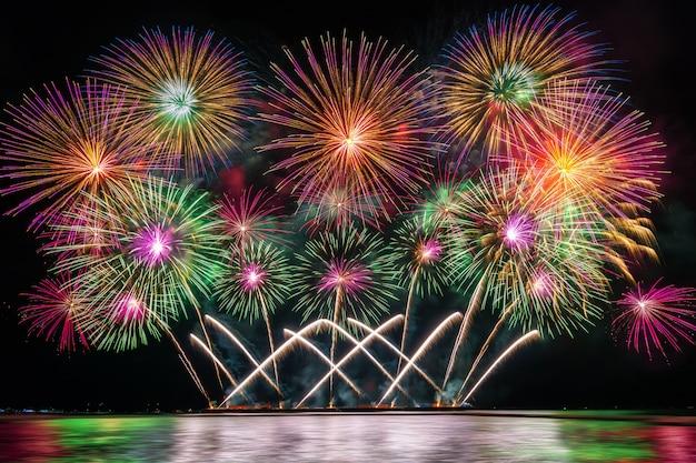Erstaunliche bunte feuerwerke, die für feier vom großen boot über dem meer explodieren