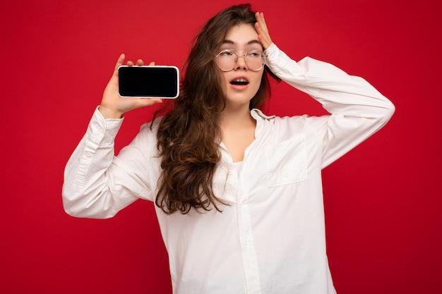 Erstaunliche charmante junge brunetfrau, die weißes hemd und optische brille trägt, lokalisiert über rotem hintergrund