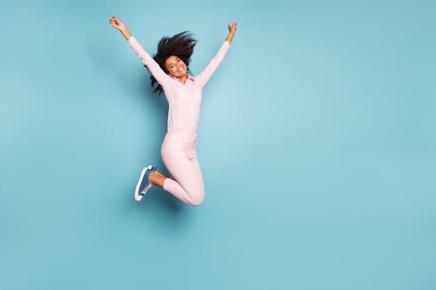 Erstaunliche dame, die hoch gespreizte hände springt