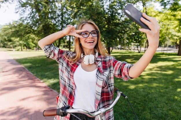 Erstaunliche dame mit weißen kopfhörern, die mit vergnügen am sommertag aufwerfen. debonair frau, die selfie macht, während auf fahrrad sitzt.