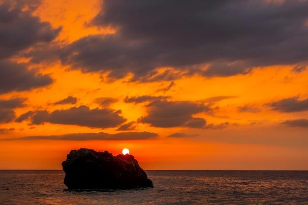 Erstaunliche farben am bewölkten himmel. sonnenuntergang über einem einsamen felsen in ruhiger see