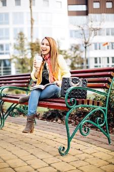 Erstaunliche frau, die draußen auf einer bank sitzt und eine zeitschrift liest