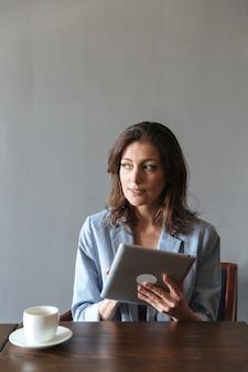 Erstaunliche frau, die drinnen mit tablet-computer sitzt.