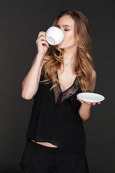 Erstaunliche frau, die kaffee trinkt und aufwirft