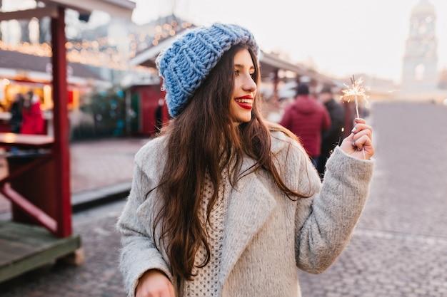 Erstaunliche frau im grauen mantel und im blauen hut, die mit wunderkerze die straße entlang gehen. entzückende weibliche frau im winteroutfit, die zeit im freien verbringt und bengallicht mit lächeln betrachtet.