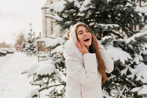 Erstaunliche frau in den weißen kleidern, die spaß am wintertag haben und für foto aufwerfen. außenporträt der erfreuten kaukasischen frau an der verschneiten straße neben fichte.