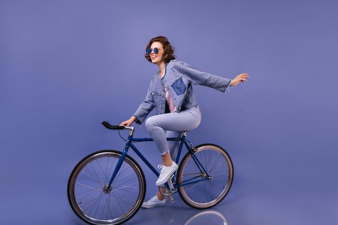 Erstaunliche frau in der frühlingskleidung, die auf fahrrad sitzt. innenporträt des reizenden mädchens in der sonnenbrille, die herumalbern.