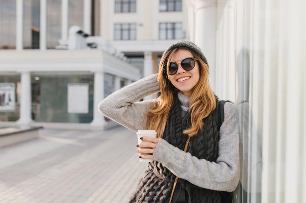 Erstaunliche frau in der stilvollen sonnenbrille mit den blonden haaren, die kaffee genießen und mit hand oben im freien aufwerfen. porträt der lächelnden frau im hut und im gestrickten sweatshirt, die am morgen auf stadtstraße stehen.
