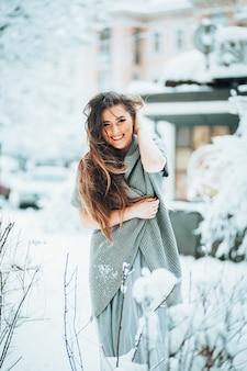 Erstaunliche Frau in einer Strickjacke und in einem hellen Kleid steht im Garten unter Büschen