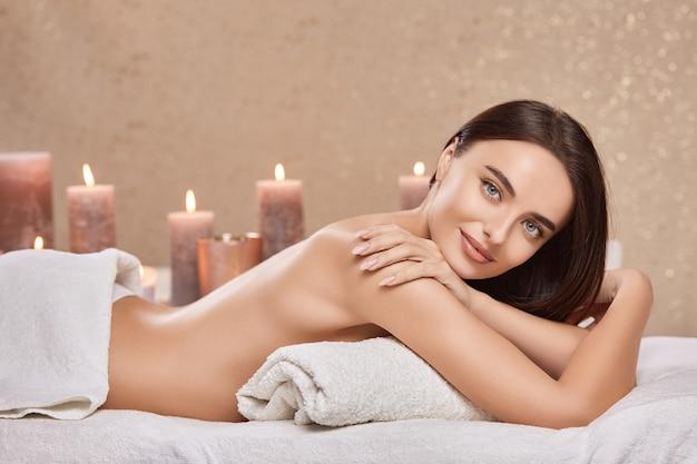Erstaunliche frau mit brünetten haaren, die glücklich und entspannt im spa liegen