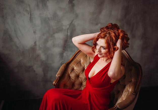 Erstaunliche frau mit dem roten haar im langen roten kleid sitzt im weichen stuhl vor dem fenster