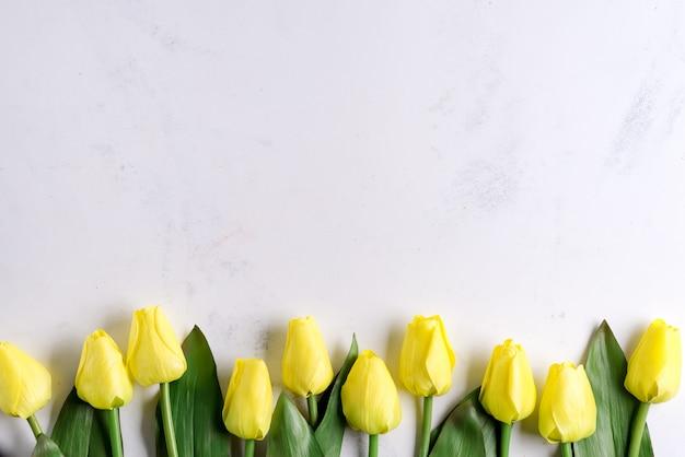 Erstaunliche frühlingsgelbe tulpenblumen auf steinhintergrund, flach liegend mit kopienraum