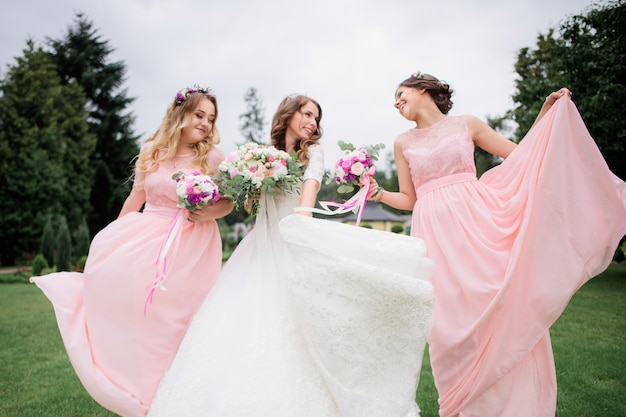 Erstaunliche junge braut und brautjungfern in den rosa kleidern mit hochzeitsblumensträußen im park