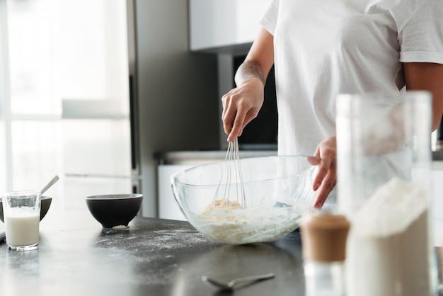 Erstaunliche junge frau, die an der küche im haus steht