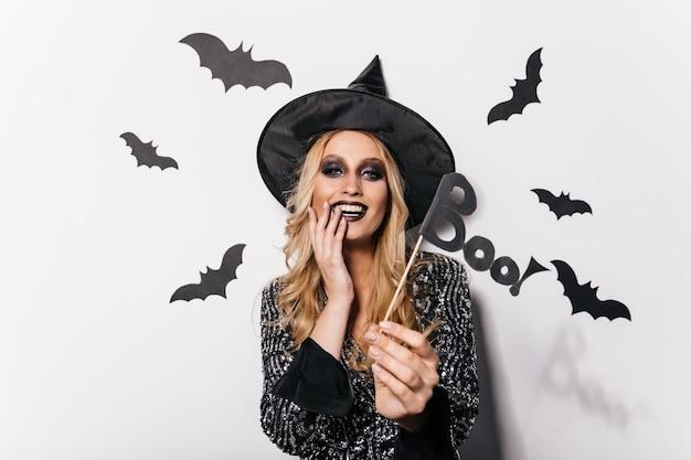 Erstaunliche junge frau, die in halloween mit fledermäusen aufwirft. attraktives blondes mädchen, das karneval genießt.