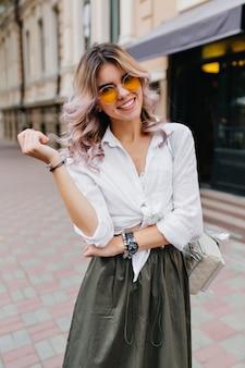 Erstaunliche junge frau im langen rock und im klassischen weißen hemd, die freizeit draußen genießt und mit vergnügen posiert