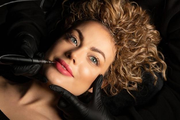 Erstaunliche junge frau mit lockigem haar mit permanentem lippen-make-up im schönheitssalon