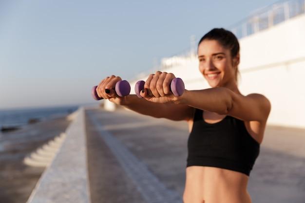 Erstaunliche junge glückliche sportfrau machen sportübungen