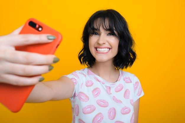 Erstaunliche kaukasische brünette, die ein selfie mit einem roten smartphone lacht, das kamera betrachtet auf lokalem gelbem hintergrund betrachtet.