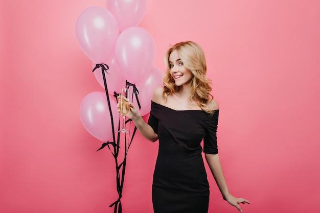 Erstaunliche kaukasische dame im eleganten schwarzen kleid, das weinglas hält und lacht. schlankes fröhliches mädchen mit champagner, das nahe rosa luftballons steht.