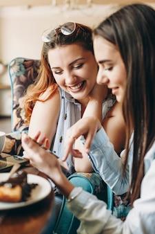 Erstaunliche kaukasische frauen in übergröße mit roten haaren, die lächelnd an einem schreibtisch sitzen und eine hand an ihrem hals halten, während sie das smartphone ihrer freundin betrachten.
