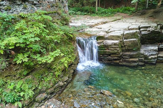 Erstaunliche landschaft des schönen wasserfalls am bergfluss mit weißem schaumwasser, das von felsigen klippen im sommerregenwald herunterfällt.