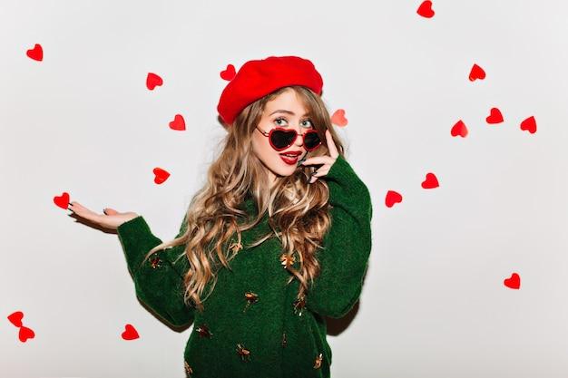 Erstaunliche lockige frau, die ihre sonnenbrille berührt und erstaunen am valentinstag ausdrückt