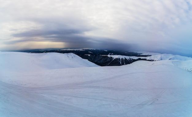 Erstaunliche luftaufnahme eines hügels bedeckt mit einer dicken schneeschicht an einem wolkigen nebligen tag