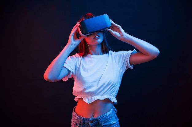 Erstaunliche moderne technologien. junge frau, die virtual-reality-brille im dunklen raum mit neonbeleuchtung verwendet