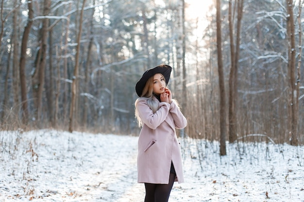 Erstaunliche modische junge frau in einem eleganten rosa mantel in einem luxuriösen hut in einem schwarzen stilvollen kleid, das in einem winterpark an einem sonnigen tag aufwirft. cooles mädchen im freien