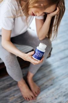 Erstaunliche pillen. müde blonde frau sitzt und schaut auf ihre schlaftabletten