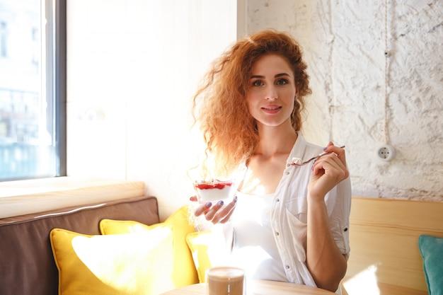 Erstaunliche rothaarige junge dame, die im café beim essen des nachtischs sitzt.