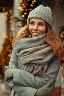 Erstaunliche schöne junge glückliche frau mit einem magischen lächeln in gestrickten kleidern in einer gestrickten grauen mütze mit einem stilvollen warmen schal auf der straße nahe den lichtern an feiertagen