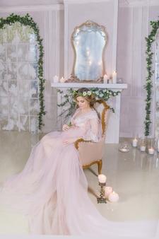 Erstaunliche schwangere frau im rosa kleid steht auf der couch still, die mit glänzenden kerzen umgeben wird