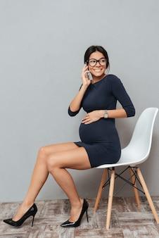 Erstaunliche schwangere geschäftsfrau, die per telefon spricht.