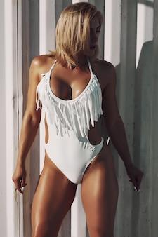 Erstaunliche sexy frau im weißen badeanzug mit perfektem sportkörper, der am strand aufwirft. konzept des körpers der sportfrau in der badebekleidung