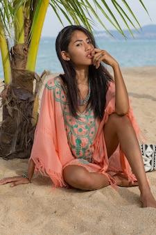 Erstaunliche sexy tan asiatische frau, die auf tropischem strand des paradieses unter dem pam baum aufwirft, auf weißem sand sitzt, sich entspannt und feiertage genießt. boho kleid mit stickerei. bali.