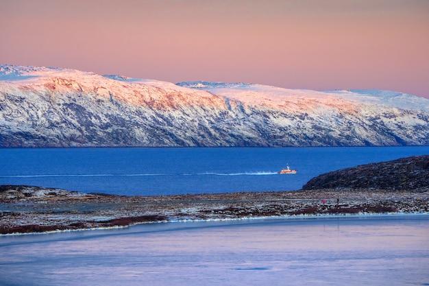 Erstaunliche sonnenaufgang-polarlandschaft mit weißer schneebedeckter bergkette am horizont. wunderbare berglandschaft auf der barentssee. teriberka.