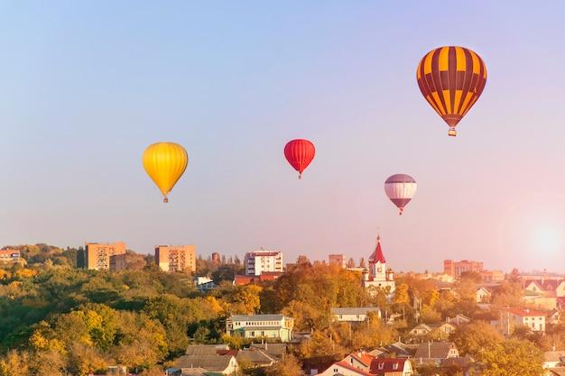 Erstaunliche stadt - bunte heißluftballone fliegen glühenden sonnenuntergang
