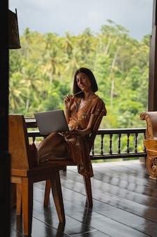 Erstaunliche weibliche person, die in einem bungalow sitzt und in ihrem blog über bali auf distanz arbeitet