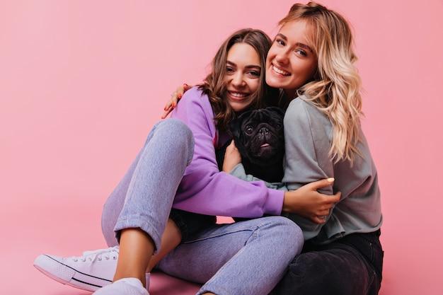 Erstaunliche weiße schwestern, die während des porträtschießens mit welpen umarmen. schöne junge damen, die auf rosa mit niedlicher bulldogge sitzen.