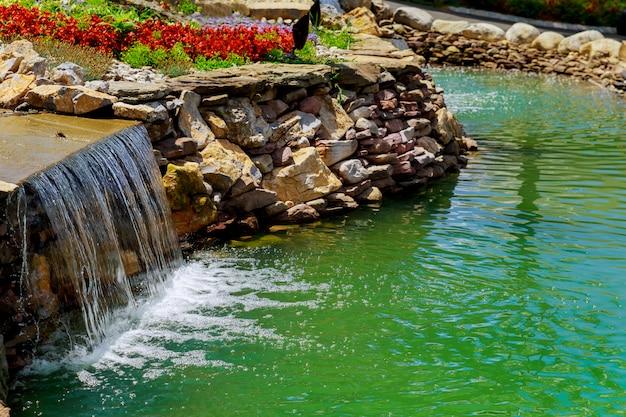 Erstaunlicher azurblauer see des wasserfalls mit haarscharfem wasser unter grünen wäldern