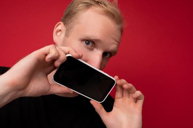 Erstaunlicher gutaussehender blonder erwachsener mann mit schwarzem t-shirt, der isoliert auf rotem hintergrund steht, mit kopienraum, der das smartphone hält und das telefon in der hand mit leerem bildschirm für das modell mit blick auf die kamera zeigt.