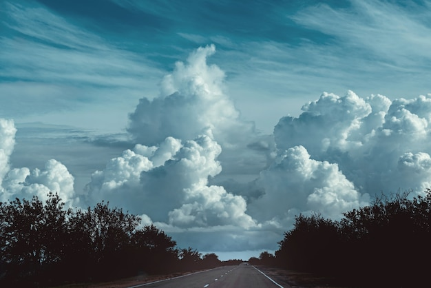 Erstaunlicher himmel mit großen dunklen wolken und straßenlandschaft