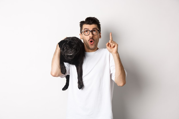 Erstaunlicher hübscher mann in der brille, niedlichen schwarzen mops-hund auf der schulter haltend, finger oben auf promo-logo zeigend, über weiß stehend.