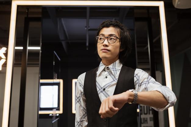 Erstaunlicher junger asiatischer mann, der brille trägt, schaut auf uhr.
