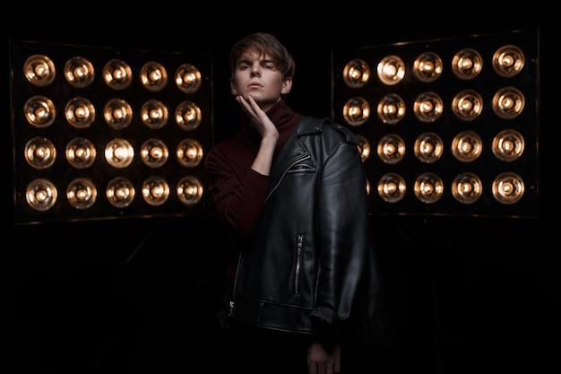 Erstaunlicher junger mann mit einer modischen frisur in einer schwarzen modischen jacke in rotem, stilvollem golf und schwarzen jeans steht und posiert in einem dunklen raum in der nähe von hellen elektrischen vintage-lampen. süßer junge Premium Fotos