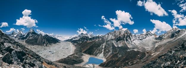 Erstaunlicher panoramablick auf den mächtigen himalaya und den friedlichen gokyo-see auf dem blauen hintergrund des bewölkten himmels. everest base camp trek im sagarmatha nationalpark im nordosten nepals.