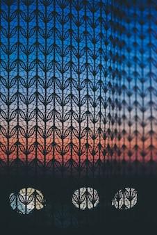 Erstaunlicher romantischer sonnenuntergang im fenster hinter silhouetten der tüllbeschaffenheit. wundervoller grapefruitblauer morgenhimmel vom fenster durch gemusterten vorhang.